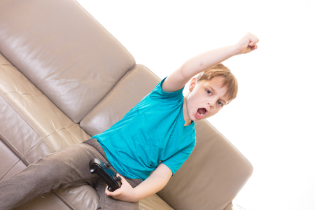 Little boy playing some video games at home using a controller, making different expressions. Imagens