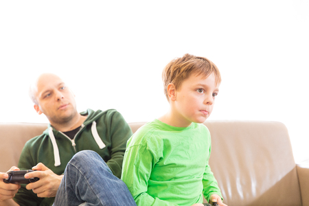 Father and son playing video games, making different facial expressions during competitive gaming, celebrating, fighting, congratulating. Stock Photo