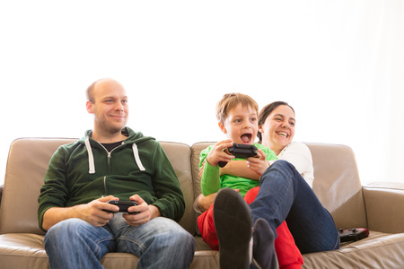 Parents playing video games with son, making different facial expressions. Imagens