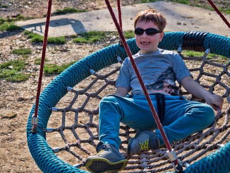 Little boy enyoing time in park lying in a swing.