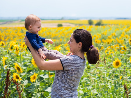 Woman and baby girl in the sunflower field in summer.