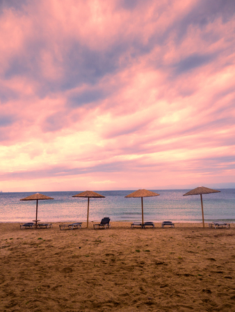 unoccupied: Beautiful sandy beach with umbrellas and sunbeds at sunset, with wonderful colors in the sky, Greek island of Thassos, Pachis beach.