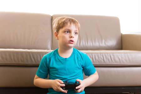 Little boy playing some video games at home using a controller, making different expressions. 版權商用圖片