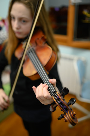 Eleven year old girl playing and practicing violin at home.