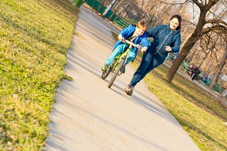 Little toddler boy learning to ride a bike with his mother.