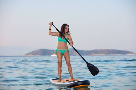 Young, attractive brunette in turquoise bikini riding and posing on a stand up paddle board (SUP) during summer vacation on the Greek seaside, island of Thasos.