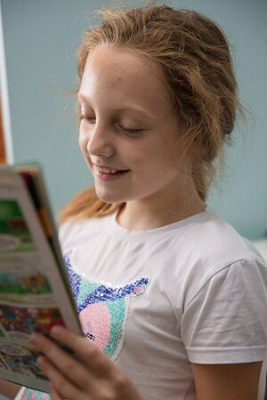 Little ten year old schoolgirl reading a magazine at home, having fun. 版權商用圖片