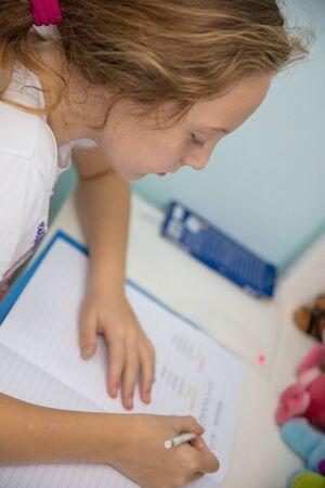 Little ten year old schoolgirl doing a homework at her desk table.
