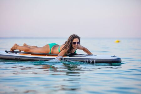 Young, attractive brunette woman, wearing turquoise bikini, posing on a stand up paddle board, Aegean sea, Thasos, Greece.