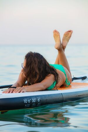 Young, attractive brunette woman, wearing turquoise bikini, posing on a stand up paddle board, Aegean sea, Thasos, Greece. Reklamní fotografie
