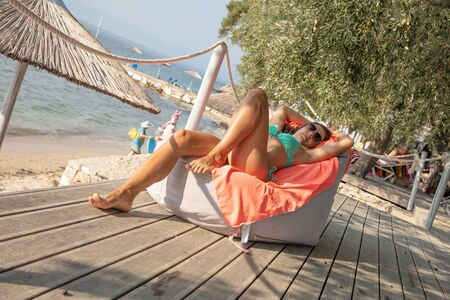 Young, attractive brunette in turquoise bikini lying and relaxing at the seaside of Greece, Thasos island.
