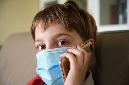 Little 9 year old boy in home isolation because of Covid 19 virus, wearing protective mask and talking on his cellphone. Banque d'images