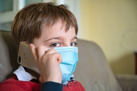 Little 9 year old boy in home isolation because of Covid 10 virus, wearing protective mask and talking on his cellphone.
