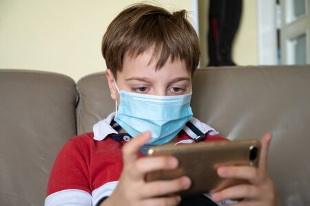 Little 9 year old boy in home isolation because of Covid 10 virus, wearing protective mask and playing video games on his cellphone.