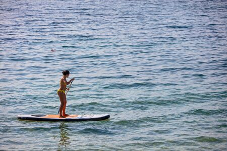Young, attractive brunette in yellow bikini riding a stand up paddleboard (SUP) at sunset, at the seaside of Greek island of Thasos.