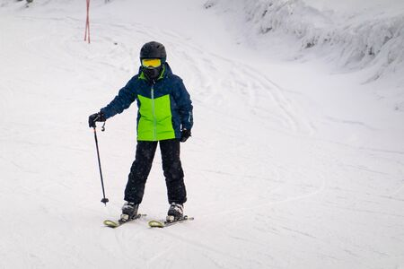 Little 9 year old boy skiing down the hill in blue green ski suit.