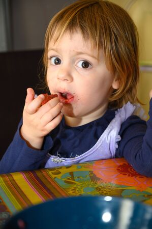 Little 3 year old girl eating strawberries at home, making different facial expressions. Zdjęcie Seryjne