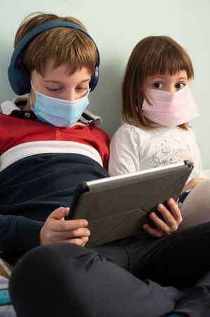 Little 9 year old boy and 3 year old girl in home isolation, quarantine because of the Covid 19 virus inffection, wearing protective mask and headphones, playing with tablet and cellphone.