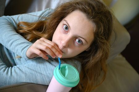 A 12 year old girl drinking juice with a straw from a cup at home. Banco de Imagens