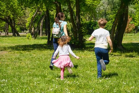 Mother running with her 9 year old son adn 4 year old daughter outdoors on green grass in spring time. Foto de archivo