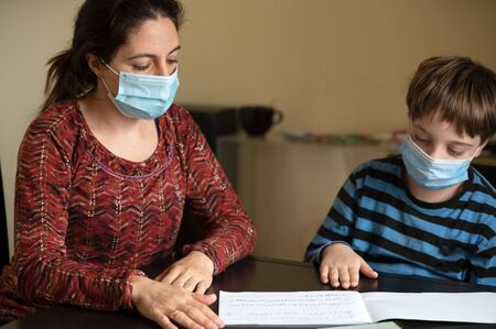 Little 9 year old boy, doing homework for music school in solfeggio with his mother, both wearing protective face masks as a prevention from covid 19 coronavirus in home quarantine.