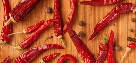 Red chili peppers on a wooden board.