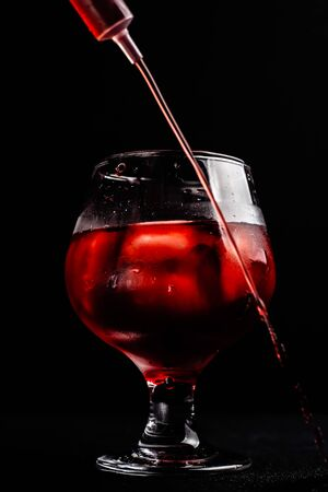Bloody alcoholic cocktail with a syringe.