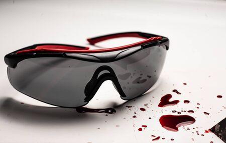 Safety breach concept. Blood on the desktop, safety glasses. Standard-Bild - 131208159