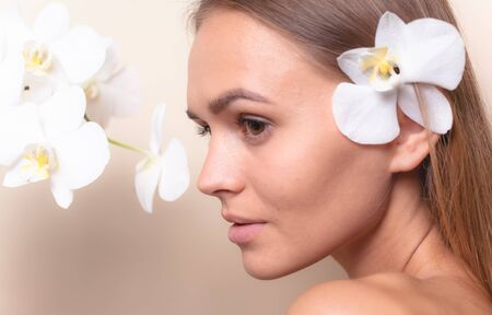 Closeup portrait of a beautiful model with white orchid flowers.