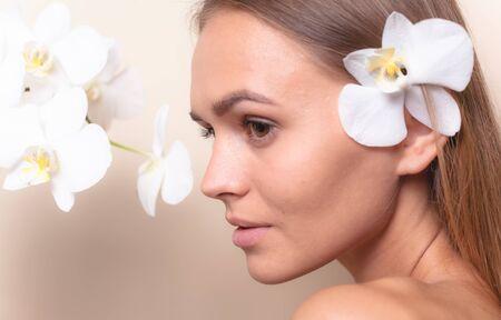 Ritratto del primo piano di una bellissima modella con fiori di orchidea bianca.