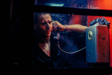 A man of criminal appearance in a payphone booth at night. Talking on the phone with a revolver and a cigarette.