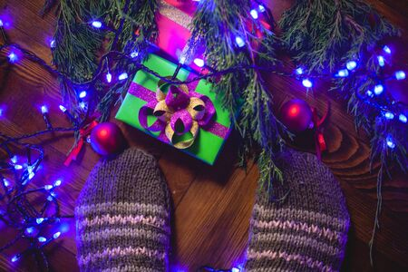 I stand in knitted socks near the Christmas tree with gifts. Stock fotó
