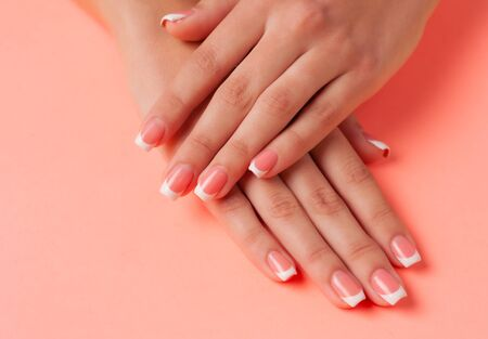 French manicure on the young hands of a girl. Flat lay photo, with place for text.