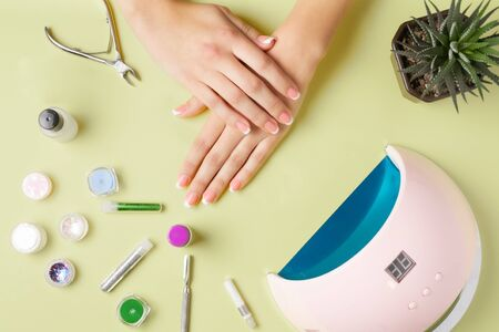 Composition for nail care, female young hands, French manicure, gel polish, lamp for nails and equipment for nail care. Flat lay photo.