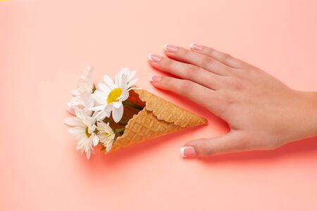 Slender young hands hold flowers, with a thin wrist, clean skin and French manicure. Flat lay photo, with place for text.
