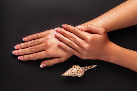 French manicure gellak. Sterk en gezond nagelsconcept. Mooie vrouwelijke handen op een zwarte achtergrond met een cockleshell.