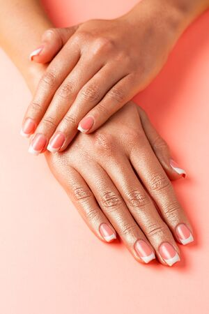 Stylish trendy french manicure. Hands of a beautiful young woman are covered by highlight on a pink background.
