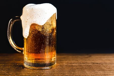 Cold beer with foam in a mug, on a wooden table and a dark background with blank space for text. Stock Photo mug of cold foamy beer close-up. Standard-Bild - 134080036