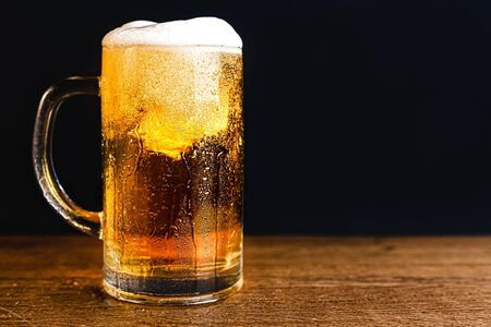 Cold beer with foam in a mug, on a wooden table and a dark background with blank space for text. Stock Photo mug of cold foamy beer close-up. Standard-Bild - 134080229
