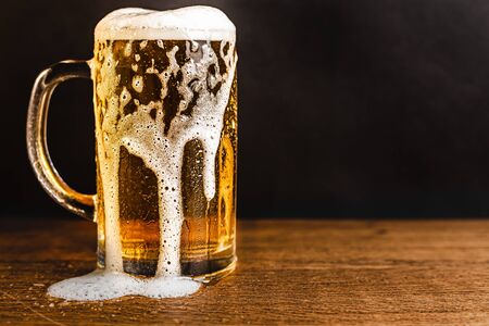 Cold beer with foam in a mug, on a wooden table and a dark background with blank space for  text. Stock Photo mug of cold foamy beer close-up. Standard-Bild - 134080244