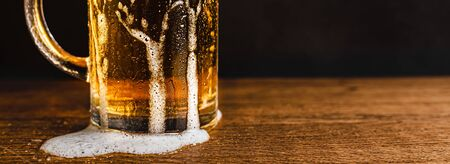 Cold beer with foam in a mug, on a wooden table and a dark background with blank space for  text. Stock Photo mug of cold foamy beer close-up. Standard-Bild - 134080256
