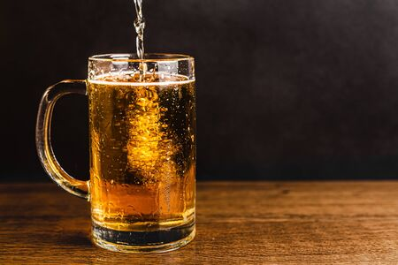 Cold beer with foam in a mug, on a wooden table and a dark background with blank space for  text. Stock Photo mug of cold foamy beer close-up. Standard-Bild - 134080546
