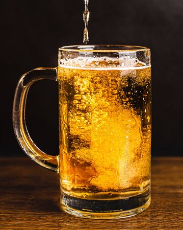 Cold beer with foam in a mug, on a wooden table and a dark background with blank space for  text. Stock Photo mug of cold foamy beer close-up. Standard-Bild - 134080558