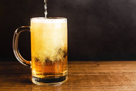 Cold beer with foam in a mug, on a wooden table and a dark background with blank space for  text. Stock Photo mug of cold foamy beer close-up. Standard-Bild - 134080584