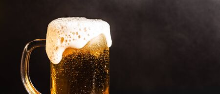 Cold beer with foam in a mug, on a wooden table and a dark background with blank space for  text. Stock Photo mug of cold foamy beer close-up. Standard-Bild - 134080602