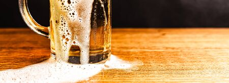 Cold beer with foam in a mug, on a wooden table and a dark background with blank space for  text. Stock Photo mug of cold foamy beer close-up. Standard-Bild - 134080613