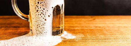 Cold beer with foam in a mug, on a wooden table and a dark background with blank space for  text. Stock Photo mug of cold foamy beer close-up. Standard-Bild - 134080627