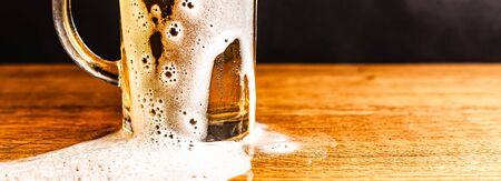 Cold beer with foam in a mug, on a wooden table and a dark background with blank space for  text. Stock Photo mug of cold foamy beer close-up. Standard-Bild - 134080631