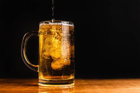 Cold beer with foam in a mug, on a wooden table and a dark background with blank space for  text. Stock Photo mug of cold foamy beer close-up. Standard-Bild - 134080649