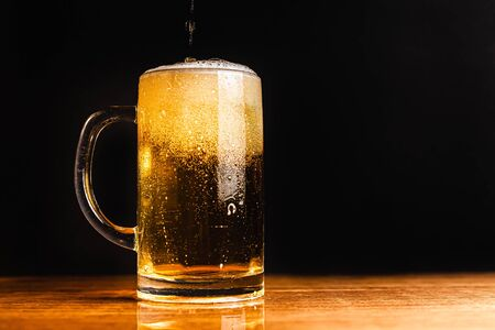Cold beer with foam in a mug, on a wooden table and a dark background with blank space for  text. Stock Photo mug of cold foamy beer close-up. Standard-Bild - 134080672
